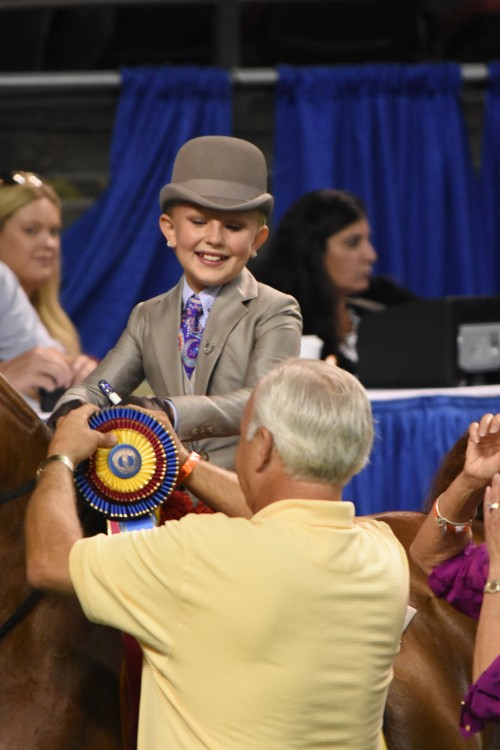 Bill Waller pins the ribbon on WalkTrot Equitation 9 10 Years Old Worlds Champion of Champions Molly Crim